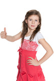 Young girl in red dress holds her thumb up
