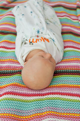 Little baby naked in a bed with colorful backgroun blanket