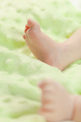 Little baby feet naked in a bed with green background