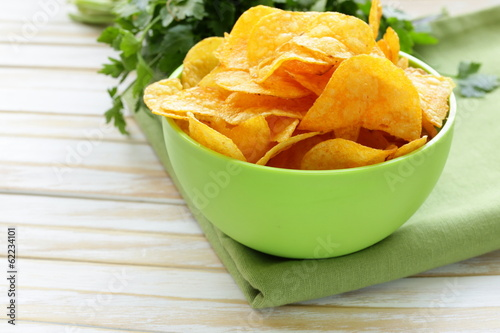 natural potato chips with paprika in a bowl on a wooden table