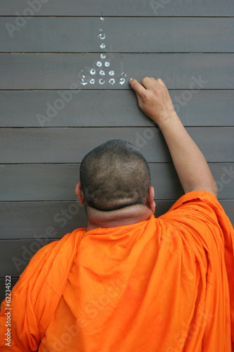 Thai monk anoints, doing Buddhist ceremony