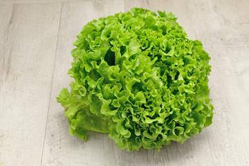 cespo d'insalata verde posta su un tavolo di legno