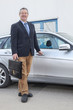 Businessman standing on the car