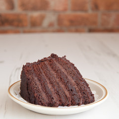 A piece of chocolaste fudge cake on a brick wall background, sel
