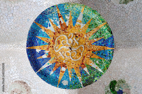 Season mosaic with orange sun at sala Hipostila in Park Guell at