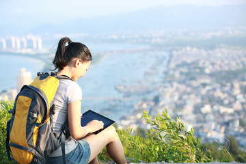 woman hiker use tablet seaside mountain peak