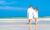 Front view of young happy caucasian couple in white walking on
