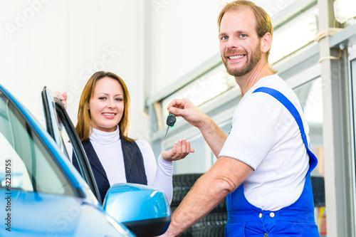 Kundin und Mechaniker an Auto in Werkstatt