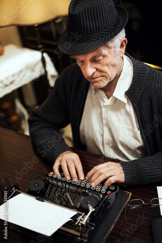 Retro Senior man writing on Obsolete Typewriter.