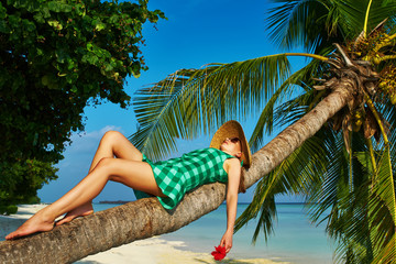 Woman lying down on a palm tree at tropical beach