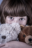 girl with freckles and two stuffed animals, teddy bears