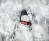Mystery, covered with white lace veil, red makeup man mask