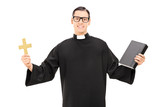 Catholic priest holding holy bible and a golden cross