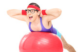 Nerdy guy doing an exercise on a pilates ball