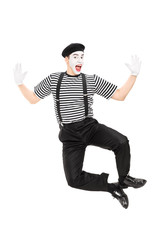 Full length portrait of mime artist jumping with joy