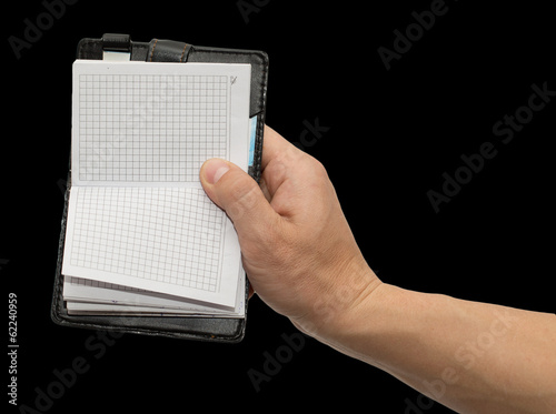 notebook in hand on a black background