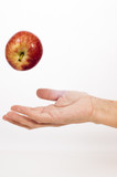 hand bouncing a red apple