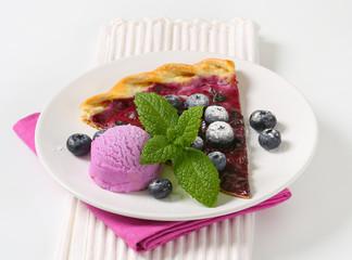 Slice of blueberry tart with ice cream