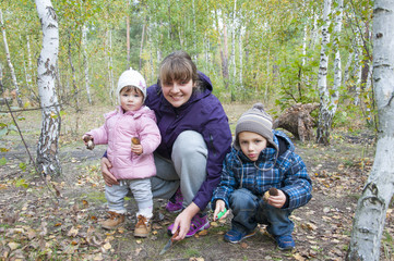 Pickers.  Mom with son and little daughter in the forest are ho