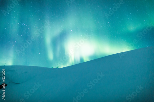 Aurora borealis (Northern lights) over snowy hill