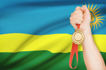 Medal in hand with flag on background - Republic of Rwanda