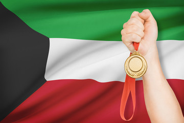 Medal in hand with flag on background - State of Kuwait