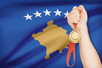 Medal in hand with flag on background - Kosovo