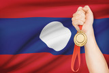 Medal in hand with flag - Lao People's Democratic Republic