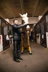Full length portrait of man in suit stroking brown horse
