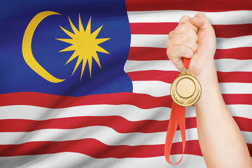 Medal in hand with flag on background - Malaysia