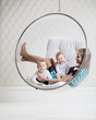 Young woman with two babies in swinging hanging chair