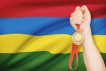 Medal in hand with flag on background - Republic of Mauritius