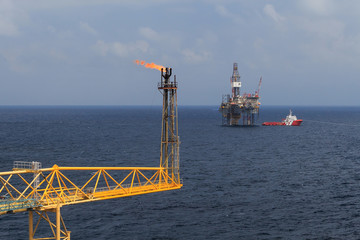 Jack up drilling rig, flare boom, and crew boat