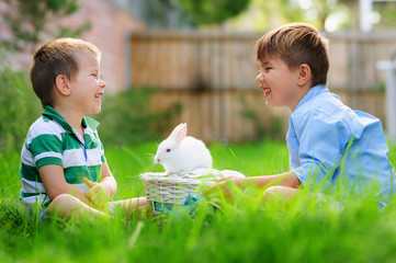two happy boys play with real easter bunny on green grass