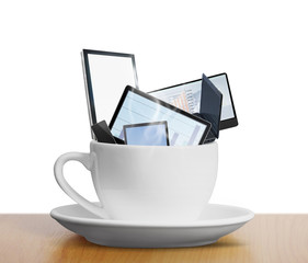 tablet touch computer gadget in cup of coffee