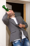 Drunk guy with a bottle of vine indoors