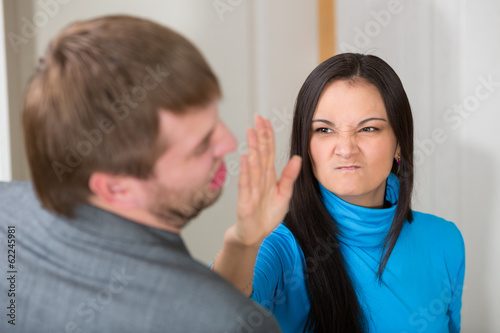 Woman about to slap her partner in living room