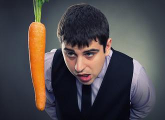 Bait metaphor. Man looking at carrot