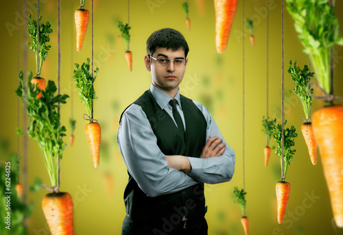 Businessman and carrots around on yellow background