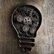 lighting bulb business concept with working gears and cogs in ru