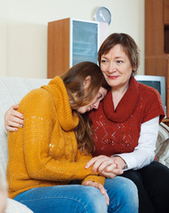 Mature mother comforting crying adult daughter