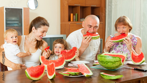 Multigeneration family  eating watermelon