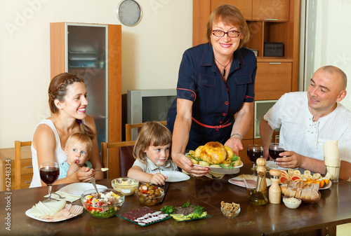 Happy multigeneration family with chicken