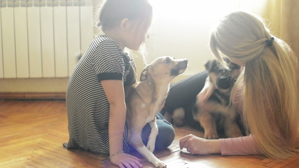 mother and daughter playing on the floor with two dogs