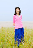 Girl standing in tall grassy field