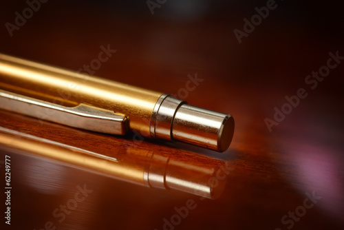 Gold pen on a varnished wooden surface with sidelights
