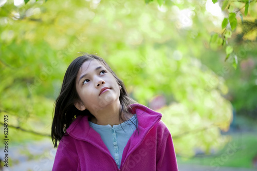 young girl looking up at autumn leaves
