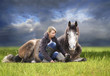 horse and woman lying in green field against  sky after storm