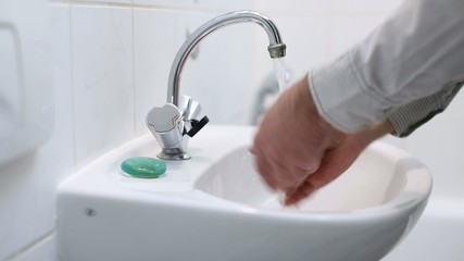 man washes his hands