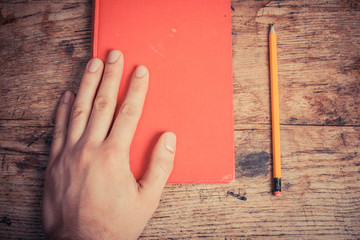 Hand with book and pencil